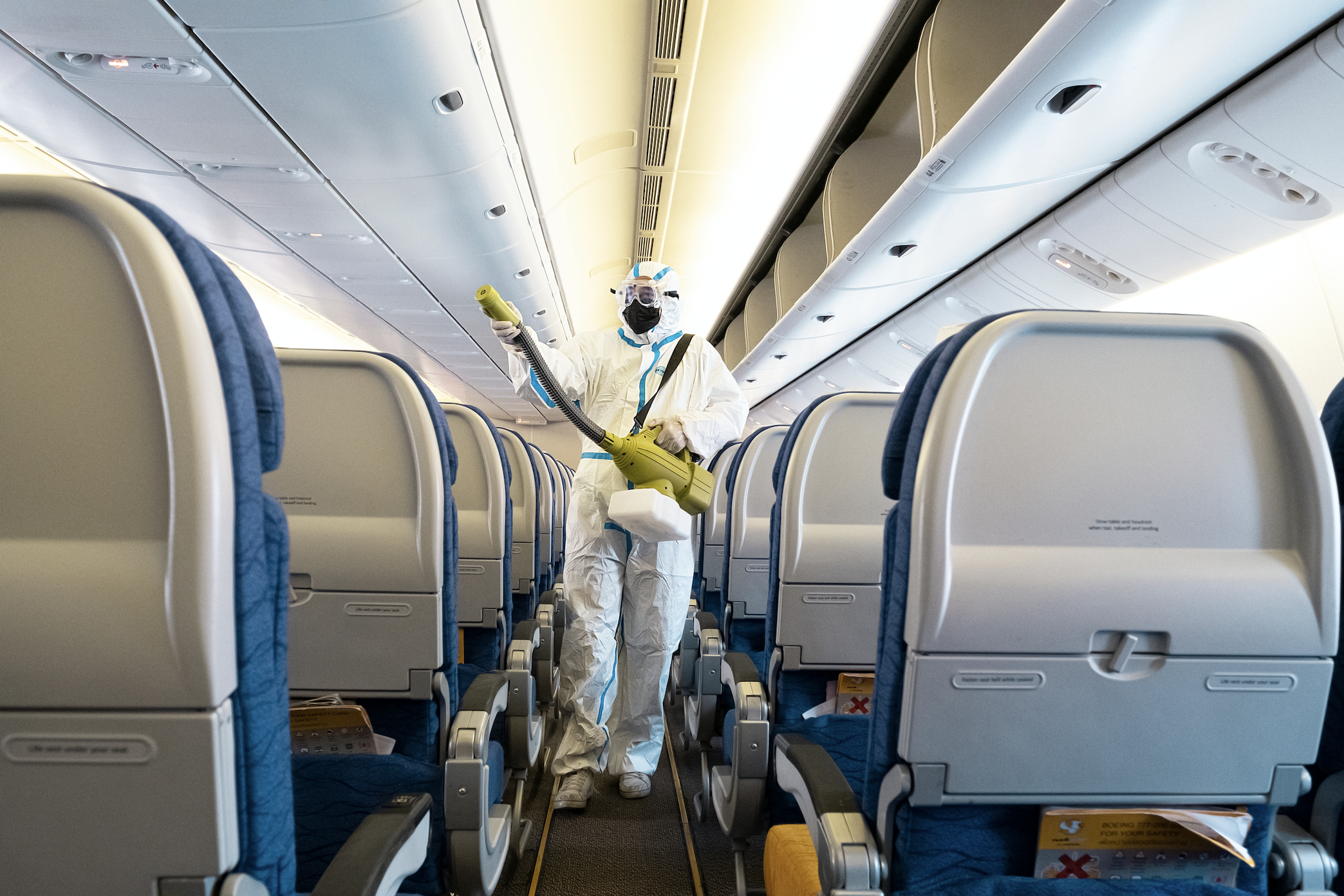 Interior of an airplane being cleaned by a sanitation worker wearing a hazmat suit.