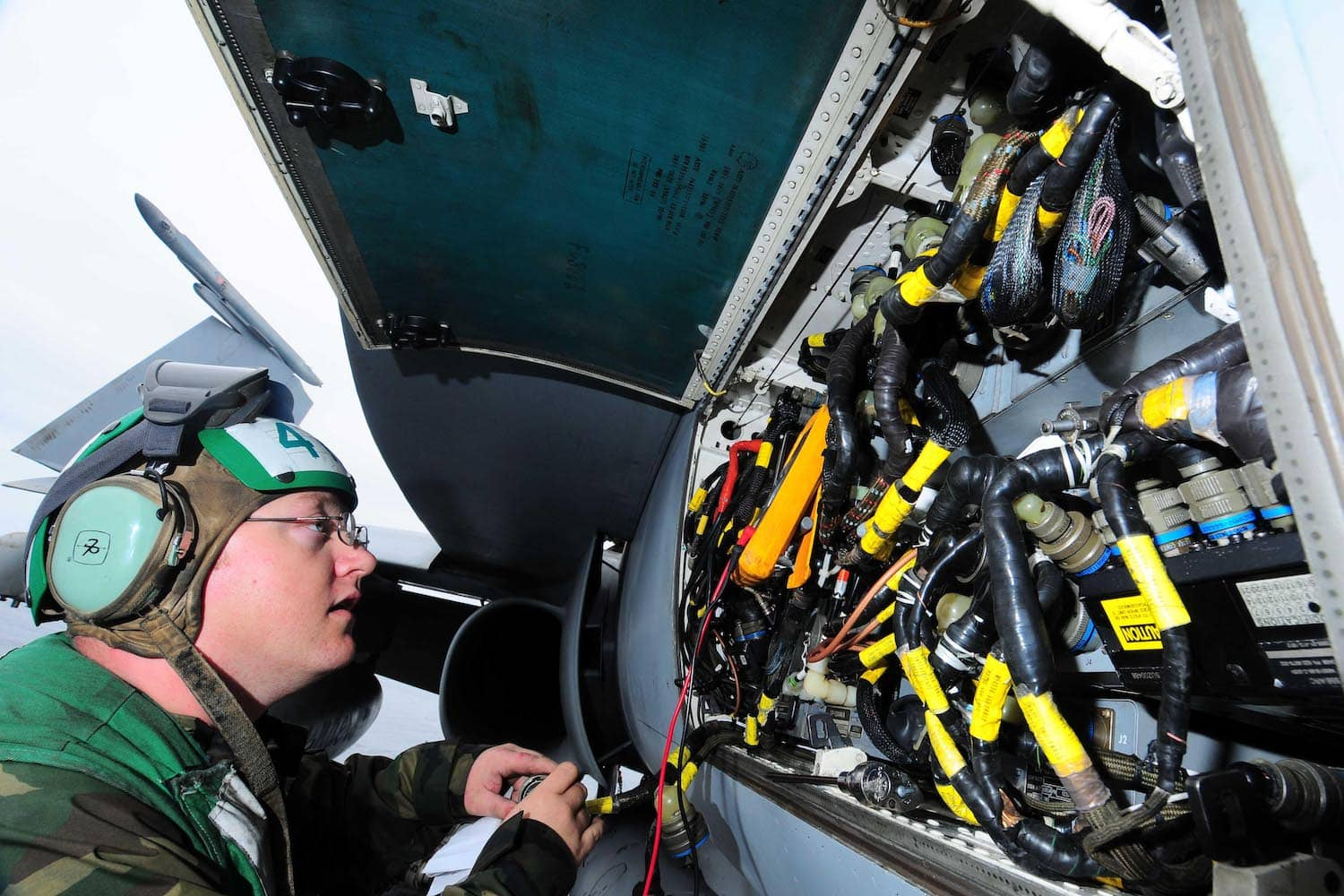 U.S. Navy Aviation Electronics Technician Inspecting the Electrical Wiring of an Aircraft